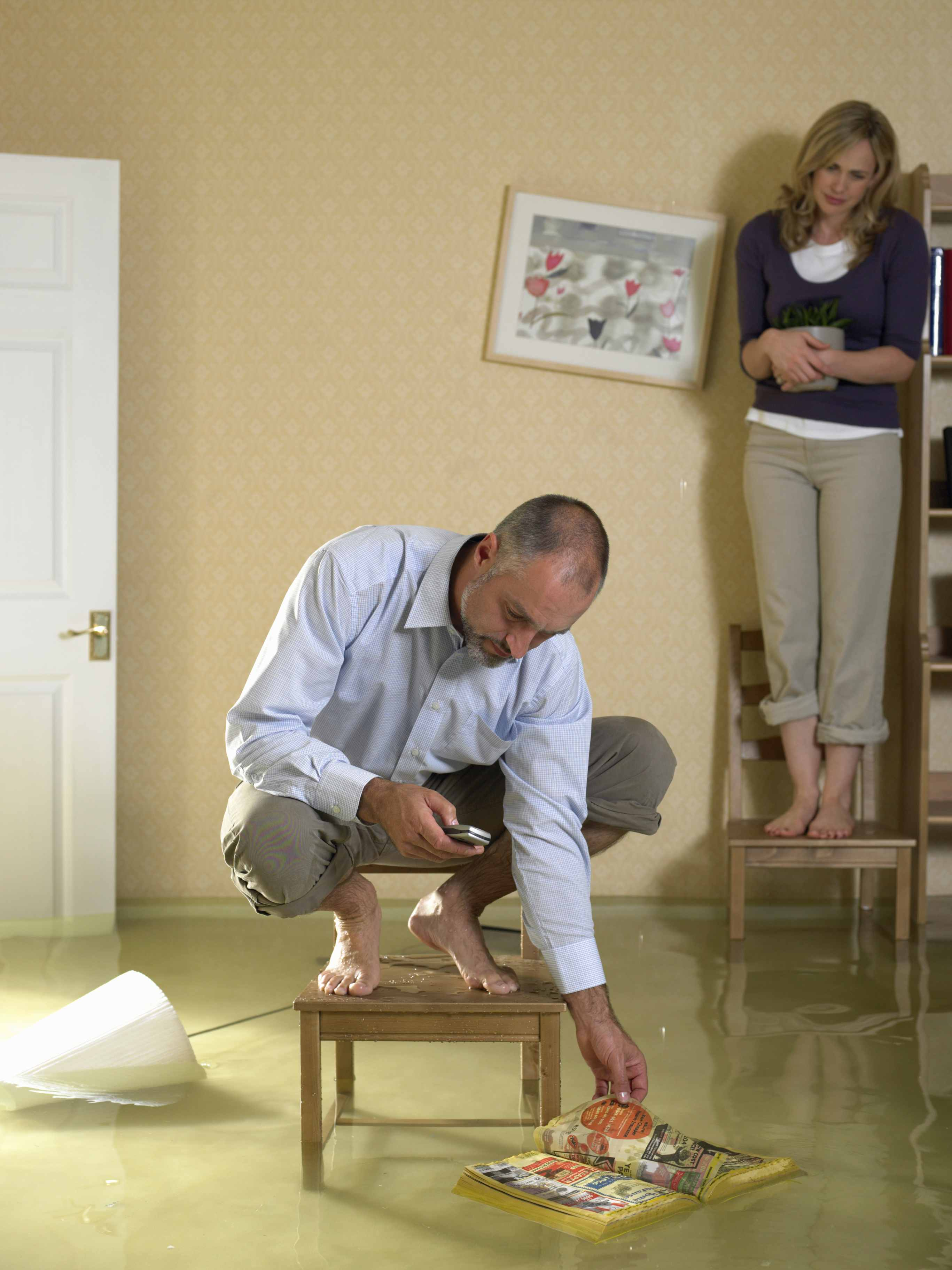 Mature man using mobile phone crouching on chair in flooded living room, mid adult woman on chair behind